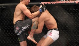 Mike Pyle (L) delivers a knee (Sherdog)