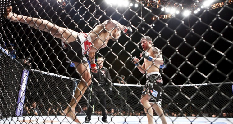 Aldo (L) pushes off the fence to throw a punch (Esther Lin/MMA Fighting)