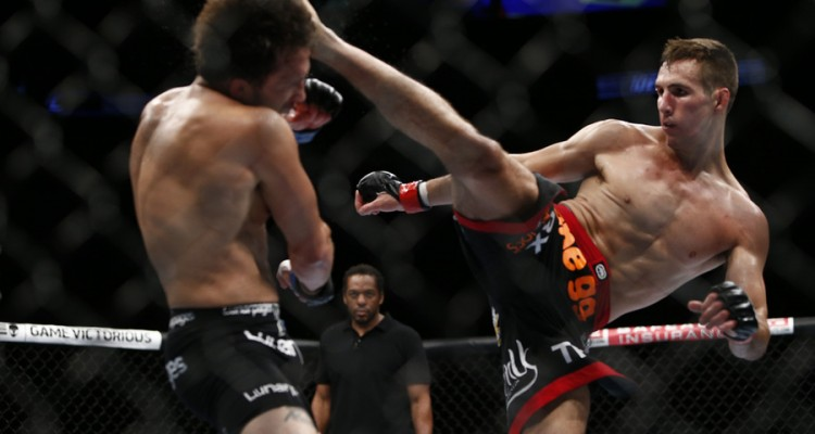 Rory MacDonald (R) lands a head kick (Esther Lin/MMA Fighting)