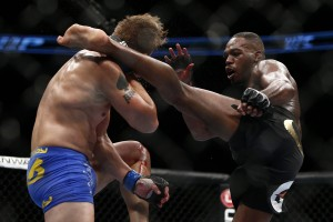 Jon Jones (R) lands a head kick (Esther Lin/MMA Fighting)