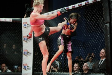 Holm (L) delivers a headkick to Hayes (R) (Will Fox/Sherdog)